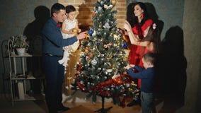 La familia alegre de cinco personas está adornando el árbol de navidad y la sonrisa almacen de video