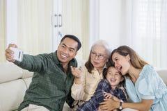 La familia alegre de tres generaciones toma el selfie en casa fotos de archivo libres de regalías