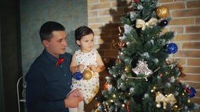 La familia alegre está adornando el árbol de navidad y la sonrisa almacen de metraje de vídeo