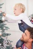 La familia alegre está preparando el árbol de navidad para Imágenes de archivo libres de regalías