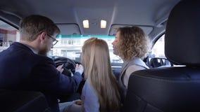La familia alegre sonriente con la muchacha dulce del niño es feliz de comprar rato del coche para examinar el automóvil en salón almacen de metraje de vídeo