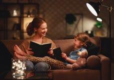 La familia antes de la madre que se va a la cama lee a su libro de la hija del ni?o cerca de una l?mpara por la tarde fotografía de archivo libre de regalías