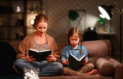 La familia antes de la madre que se va a la cama lee a su libro de la hija del ni?o cerca de una l?mpara por la tarde foto de archivo