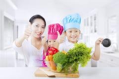 La familia asiática con los pulgares sube y las verduras Foto de archivo libre de regalías