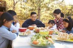 La familia asiática en una tabla en una cubierta dice un rezo antes de comer Imagen de archivo