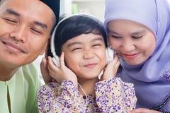 La familia asiática escucha el auricular mp3 Imágenes de archivo libres de regalías