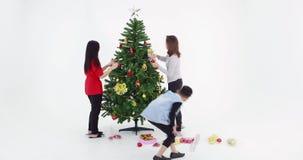 La familia asiática está adornando el árbol de navidad almacen de metraje de vídeo
