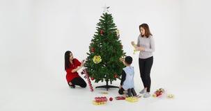 La familia asiática está adornando el árbol de navidad metrajes