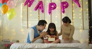 La familia asiática feliz que celebra los regalos de la abertura del cumpleaños del ` s de la hija y disfruta en cama almacen de video