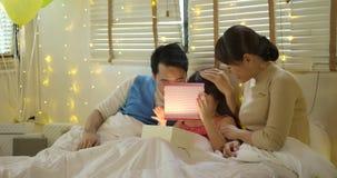 La familia asiática feliz que celebra los regalos de la abertura del cumpleaños del ` s de la hija y disfruta en cama almacen de metraje de vídeo