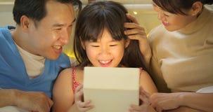 La familia asiática feliz que celebra los regalos de la abertura del cumpleaños del ` s de la hija y disfruta en cama metrajes