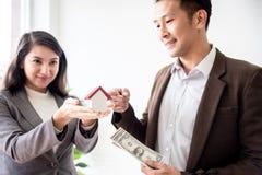 La familia asiática joven del amor de los pares de la felicidad que habla de la compra de la casa y el dueño casero discuten la imágenes de archivo libres de regalías