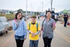 La familia asiática joven disfruta de sus momentos con los pétalos en sus manos Foto de archivo