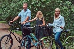 La familia atractiva se vistió en ropa casual en un paseo de la bicicleta con su pequeño perro lindo del perro de Pomerania Imagen de archivo libre de regalías