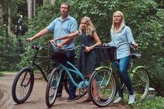 La familia atractiva se vistió en ropa casual en un paseo de la bicicleta con su pequeño perro lindo del perro de Pomerania Fotos de archivo