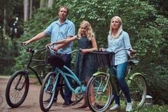La familia atractiva se vistió en ropa casual en un paseo de la bicicleta con su pequeño perro lindo del perro de Pomerania Imágenes de archivo libres de regalías