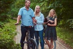 La familia atractiva se vistió en ropa casual en un paseo de la bicicleta con su pequeño perro lindo del perro de Pomerania Foto de archivo