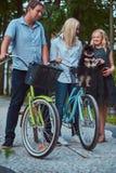 La familia atractiva se vistió en ropa casual en un paseo de la bicicleta con su pequeño perro lindo del perro de Pomerania Imagenes de archivo