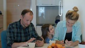 La familia bebe té en la cocina, mirada en la tableta, teléfono, hija sube almacen de video