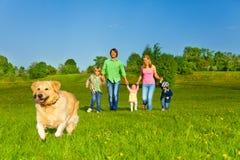La familia camina con el perro corriente en parque Imagen de archivo libre de regalías