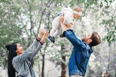 La familia camina en el parque, el padre detiene a la pequeña hija sobre su cabeza, las risas de la madre y las palmadas, la fami fotos de archivo libres de regalías