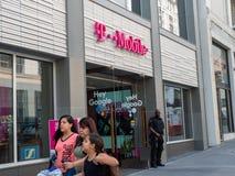 La familia camina por la tienda de T-Mobile del buque insignia en San Francisco céntrico fotos de archivo libres de regalías