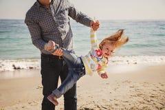 La familia cariñosa alegre feliz, el padre y la pequeña hija jugando en la playa, padre joven está deteniendo a su niño al revés Fotografía de archivo libre de regalías