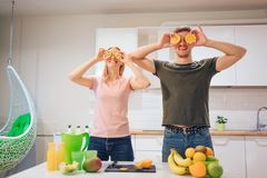La familia cariñosa joven se divierte con la naranja orgánica mientras que cocina las frutas frescas en la cocina blanca Alimento foto de archivo