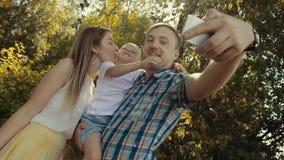 La familia cariñosa que toma la foto en madre verde del bosque besa al pequeño hijo almacen de metraje de vídeo