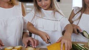 La familia caucásica en la ropa blanca está preparando la sopa usando calabacín fresco La madre atractiva está enseñando a su hij metrajes