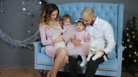 La familia celebra el Año Nuevo, padres jovenes y las hijas se divierten con los perritos mullidos blancos en el sofá en el estud almacen de metraje de vídeo