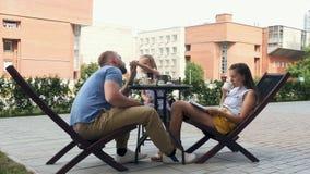 La familia cena en el café al aire libre almacen de metraje de vídeo