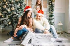 La familia cerca de la chimenea en la Navidad adornó el interior de la casa con la caja de regalo Imagen de archivo libre de regalías