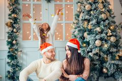 La familia cerca de la chimenea en la Navidad adornó el interior de la casa con la caja de regalo Imagen de archivo