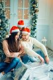 La familia cerca de la chimenea en la Navidad adornó el interior de la casa con la caja de regalo Fotos de archivo libres de regalías