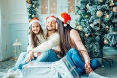 La familia cerca de la chimenea en la Navidad adornó el interior de la casa con la caja de regalo Fotografía de archivo