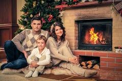 La familia cerca de la chimenea en la Navidad adornó la casa Fotos de archivo libres de regalías