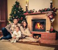 La familia cerca de la chimenea en la Navidad adornó la casa Imagen de archivo