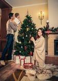La familia cerca de la chimenea en la Navidad adornó la casa Imagenes de archivo