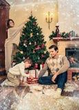 La familia cerca de la chimenea en la Navidad adornó la casa Fotografía de archivo