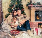La familia cerca de la chimenea en la Navidad adornó la casa Fotografía de archivo libre de regalías