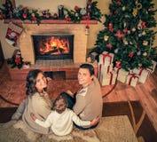 La familia cerca de la chimenea en la Navidad adornó la casa Foto de archivo