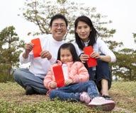 La familia china feliz que lleva a cabo rojo envuelve imagen de archivo libre de regalías