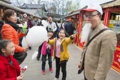 La familia china se divierte con la barba del caramelo de algodón Imagen de archivo