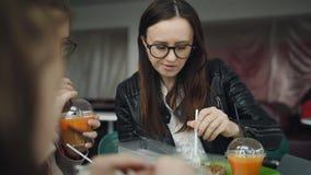 La familia come el café chino de los tallarines Madre con dos hijas en un café que almuerza y que bebe el jugo de zanahoria fre metrajes
