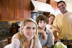 La familia con el adolescente embroma en la cocina, muchacho que frunce el ceño Fotos de archivo libres de regalías