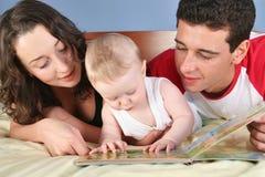 La familia con el bebé leyó el libro 2 Foto de archivo