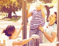 La familia con el entrenamiento del hijo adolescente encendido levanta la barra Fotos de archivo libres de regalías