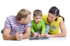 La familia con el hijo del niño leyó el libro de niños Foto de archivo