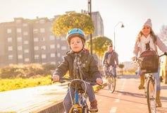 La familia con el montar a caballo del niño monta en bicicleta en la ciudad fotografía de archivo